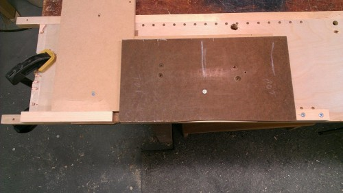 Handle secured in jig by adjustable clamping sticks on each end