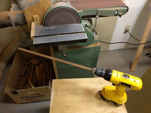 Blank mounted in drill is rough-rounded with disk sander