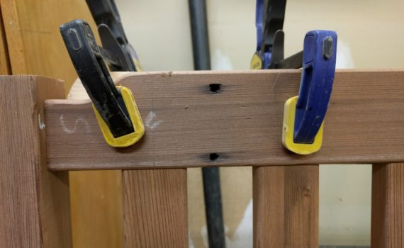 Old nail holes in top rail of redwood bench